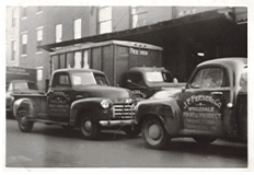 Two early 1920's Feeser's delivery trucks parked in the street facing one another.
