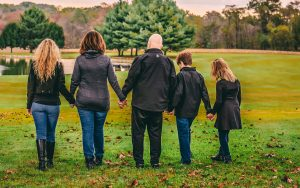 A family holding hands walking away from the camera
